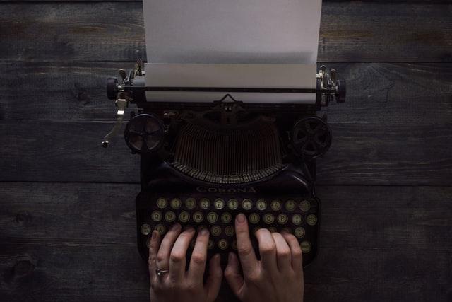 hands typing on typewriter.